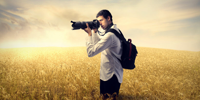 Photographer with a backpack in a field taking a picture of a sunrise.